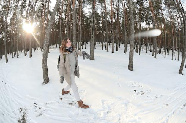Uma jovem e alegre menina caucasiana em um casaco marrom está jogando