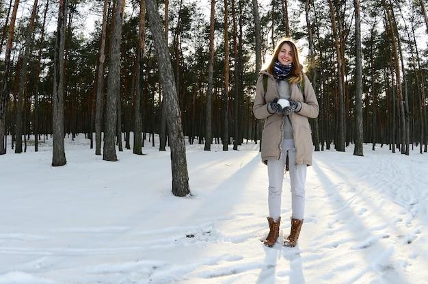 Uma jovem e alegre menina caucasiana em um casaco marrom na neve