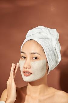 Uma jovem e atraente garota asiática com uma toalha branca na cabeça aplicou uma útil máscara de argila