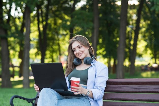 Uma jovem e atraente garota caucasiana em fones de ouvido, sentado em um banco do parque. usando um laptop. freelance, conceito de rede