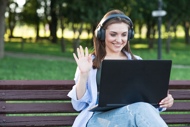 Uma jovem e atraente garota caucasiana em fones de ouvido, sentado em um banco do parque. usando um laptop. saudação, conferência à distância