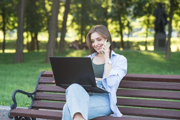 Uma jovem e atraente garota caucasiana, sentado em um banco do parque. falando ao telefone e usando um laptop. conceito freelance