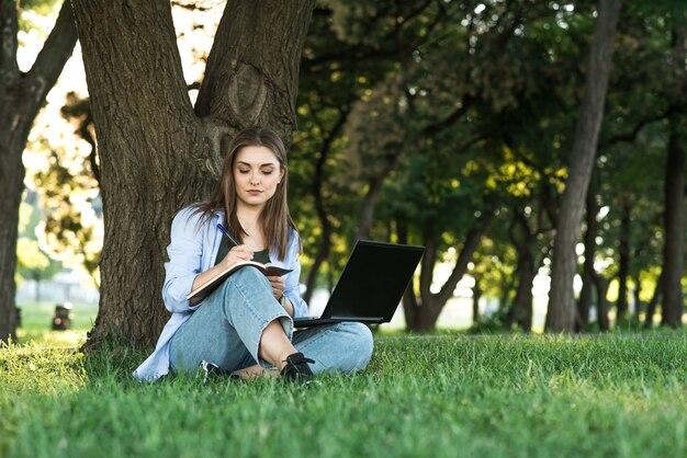 Uma jovem e atraente garota caucasiana sentado na grama no gramado e trabalhando. escrevendo em um caderno. freelance e conceito de educação