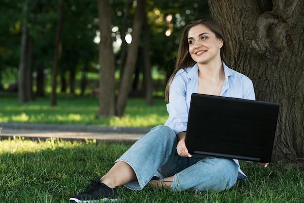 Uma jovem e atraente garota caucasiana sentado na grama no gramado e trabalhando. usando um laptop. freelance e conceito de educação.
