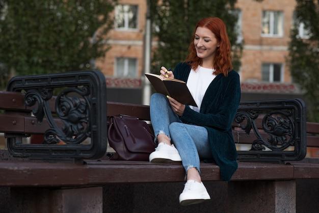 Uma jovem e atraente ruiva caucasiana, escrevendo em um caderno enquanto está sentado em um banco. conceito de educação.