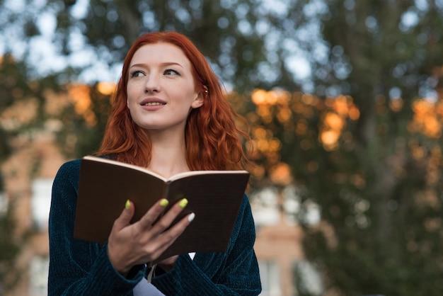 Uma jovem e atraente ruiva caucasiana está lendo um livro. conceito de educação.
