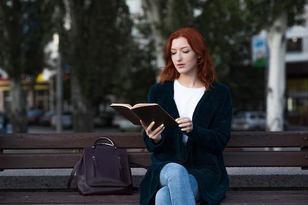 Uma jovem e atraente ruiva caucasiana está lendo um livro enquanto está sentado em um banco. conceito de educação.