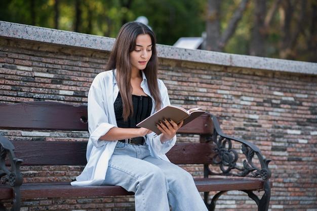 Uma jovem e bela garota árabe ou caucasiana vestida em estilo casual está lendo um livro enquanto está sentado em um banco do parque. conceito de conhecimento e educação.