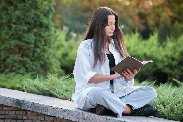 Uma jovem e bela garota árabe ou caucasiana vestida em estilo casual está lendo um livro enquanto está sentado no parque. conceito de conhecimento e educação.