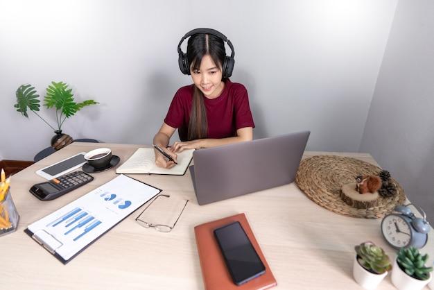 Uma jovem e bela garota asiática de negócios relaxantes usando um laptop trabalhando remotamente de casa