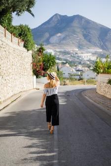 Uma jovem e bela mulher caminha pelas ruas de uma pequena cidade européia. férias de verão