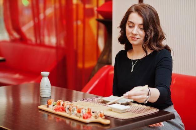 Uma jovem e bela mulher comendo sushi em um restaurante japonês tradicional
