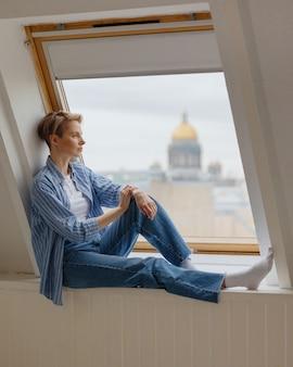 Uma jovem e bela mulher europeia com cabelo loiro curto está sentada no parapeito da janela
