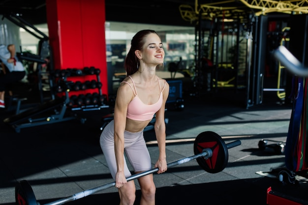 Uma jovem e bela mulher treina com uma barra no ginásio. posando com elementos para treinamento