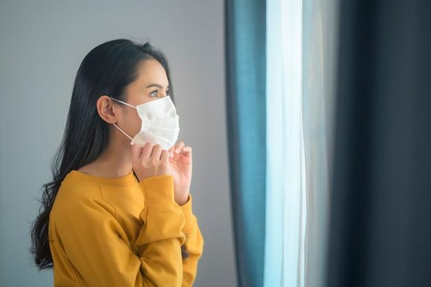 Uma jovem e bela mulher usando uma máscara protetora facial se preparando para sair, healthcare e conceito covid-19