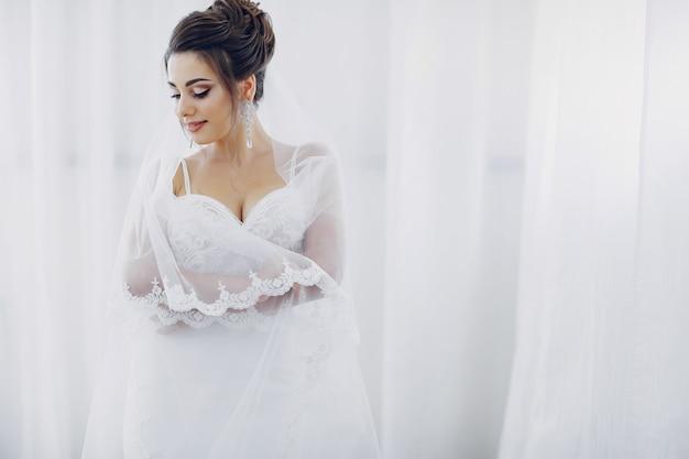 Uma jovem e bela noiva em casa vai a um casamento