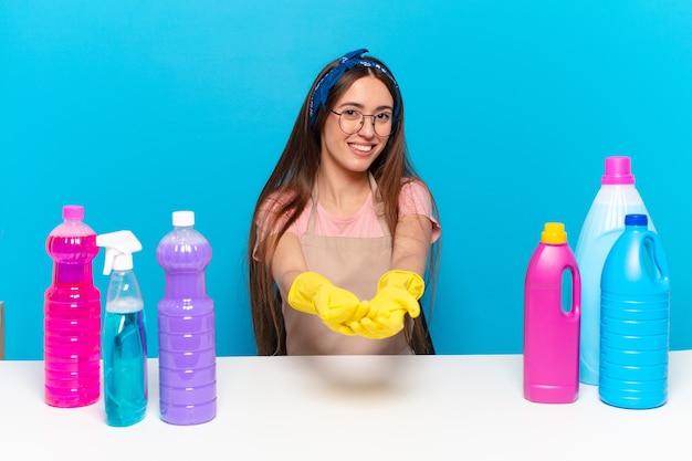 Uma jovem e bonita dona de casa sorrindo feliz com um olhar amigável, confiante e positivo, oferecendo e mostrando um objeto ou conceito