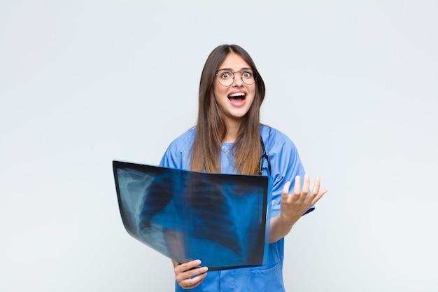 Uma jovem e bonita enfermeira parecendo desesperada e frustrada, estressada, infeliz e irritada, gritando e gritando