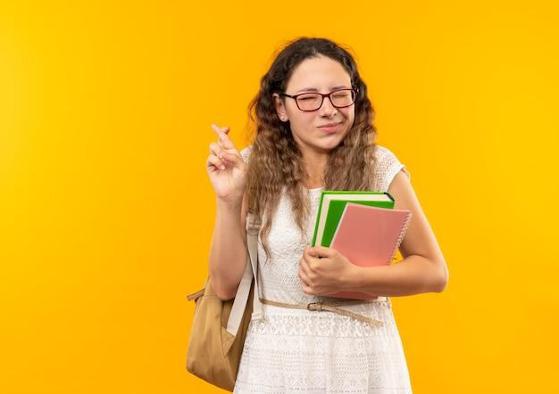 Uma jovem e bonita estudante satisfeita usando óculos e uma bolsa nas costas segurando um livro e um bloco de notas cruzando os dedos com os olhos fechados isolados na parede amarela