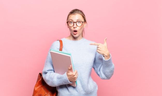 Uma jovem e bonita estudante se sentindo feliz, surpresa e orgulhosa, apontando para si mesma com um olhar animado e surpreso
