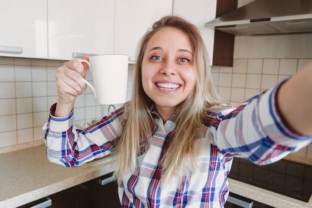 Uma jovem e bonita loira sorridente caucasiana com uma camisa xadrez e uma xícara de café ou chá branca tira uma selfie