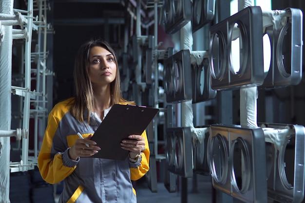 Uma jovem e bonita mulher branca trabalha na oficina de pintura da fábrica, ela verifica os produtos de metal sem pintura e registra na lista de verificação.