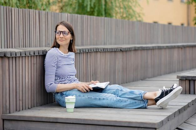 Uma jovem e confiante mulher europeia está a descansar e a ler um livro que uma mulher bebe café, relaxa ou