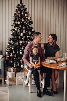 Uma jovem e feliz família de três pessoas comemora o ano novo juntos perto da árvore de natal e sorri