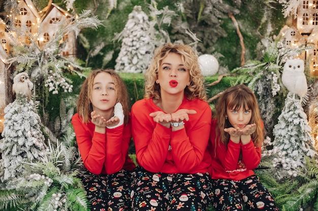 Uma jovem e linda mãe posa para a câmera com suas duas filhas no estúdio com muitas decorações de inverno