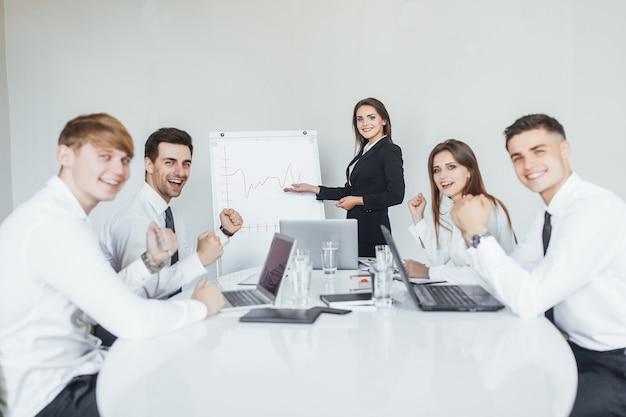 Uma jovem e moderna mulher de negócios apresenta seus colegas, sócios na moderna sala de conferências.