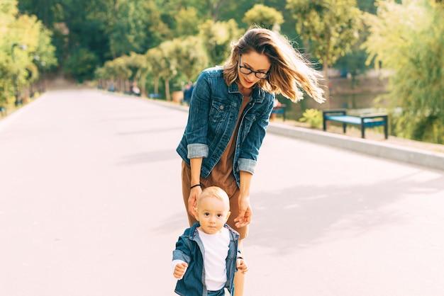 Uma jovem e seu bebê caminhando no parque