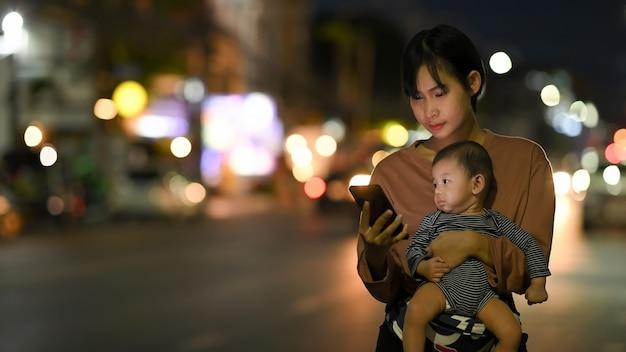 Uma jovem e um bebê estão esperando seu táxi particular enquanto usam um aplicativo de transporte em um telefone celular