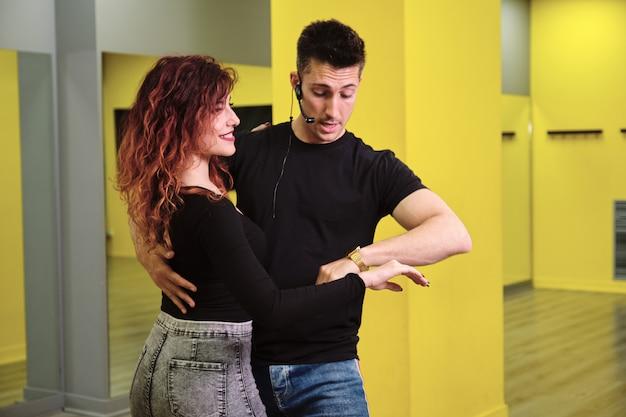 Uma jovem e um homem ensinando salsa e bachata