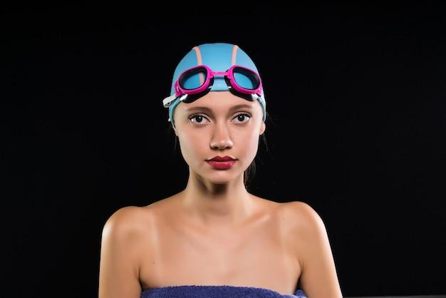 Uma jovem é uma nadadora com óculos de natação e uma touca de natação preocupada. olha para a câmera