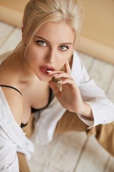 Uma jovem elegante com cabelo loiro perfeito e maquiagem da moda