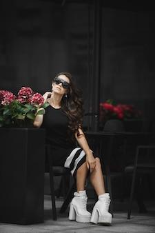 Uma jovem elegante com óculos de sol da moda e um vestido elegante, sentada à mesa do café ao ar livre