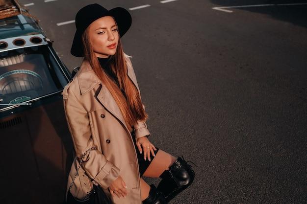 Uma jovem elegante com um casaco bege e chapéu preto em uma rua da cidade sentada no capô de um carro ao pôr do sol