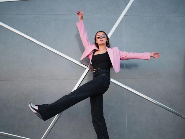 Uma jovem elegante com uma jaqueta rosa da moda e óculos escuros em uma corrente