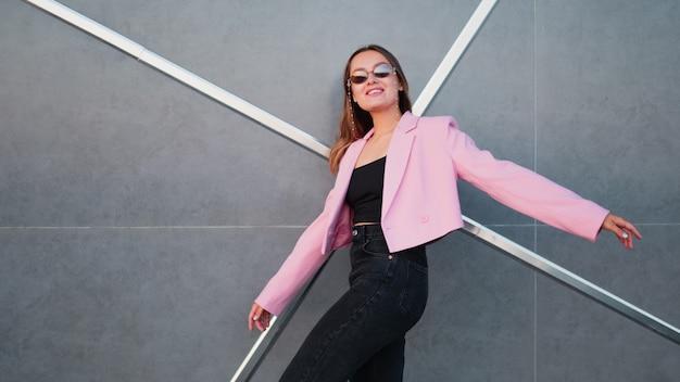 Uma jovem elegante com uma jaqueta rosa da moda e óculos escuros