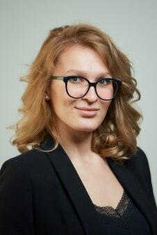 Uma jovem elegante de óculos, vestida com um terno preto com uma camisa preta. um retrato do close-up de uma senhora loira feliz que veste uma roupa de negócios.