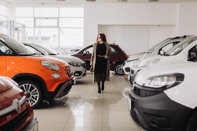 Uma jovem elegante está escolhendo um carro novo em uma loja de carros