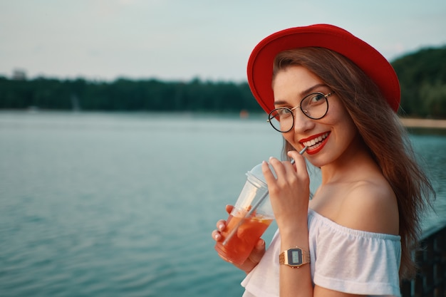 Uma jovem elegante, tomar uma bebida refrescante