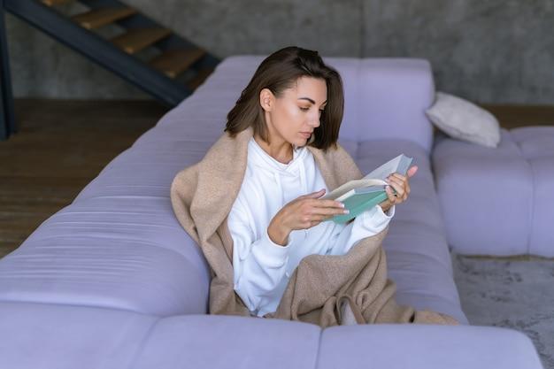 Uma jovem em casa com um moletom branco no sofá, enrolada em um cobertor quente, lê um livro