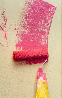 Uma jovem em close-up pinta uma parede amarela em rosa. reparação do interior.