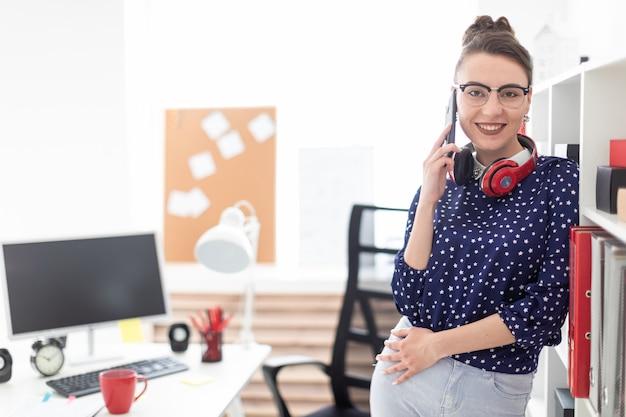 Uma jovem em copos está de pé no escritório perto do rack e falando ao telefone