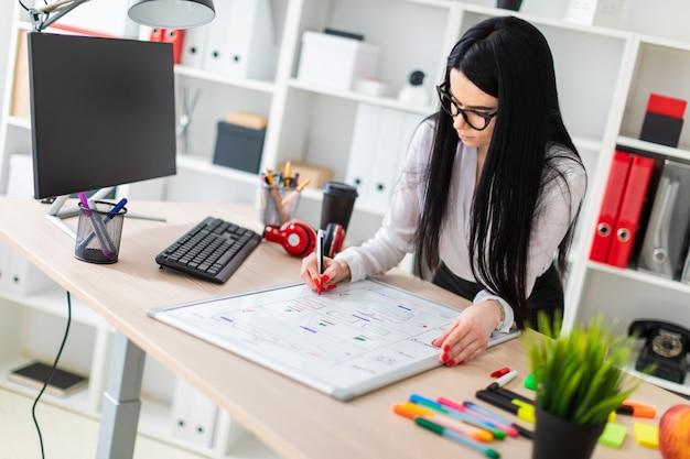 Uma jovem em copos fica perto da mesa, detém um marcador na mão e desenha em um quadro magnético.