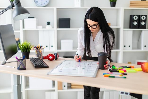 Uma jovem em copos fica perto de uma mesa, detém um copo de café na mão e desenha um marcador em um quadro magnético.
