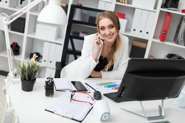 Uma jovem em fones de ouvido com um microfone se senta em uma mesa no escritório