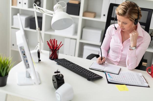 Uma jovem em fones de ouvido se senta em uma mesa no escritório, segura um lápis na mão