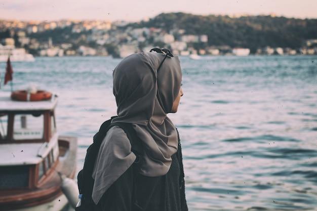 Uma jovem em hijab olhando para o sae à beira-mar.